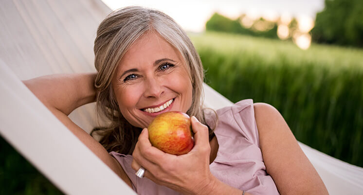 woman with implants eating apple