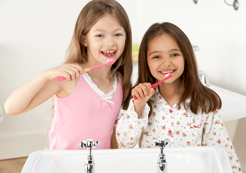 young girls brushing their teeth
