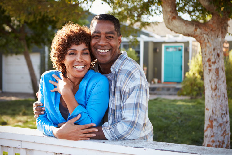 Middle-aged couple embraces and smile in front of their home after receiving professional teeth whitening