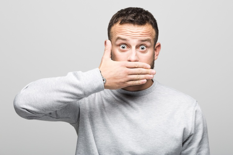 Brunette man in a gray sweater covers his mouth with his hand, saying no to dental fads