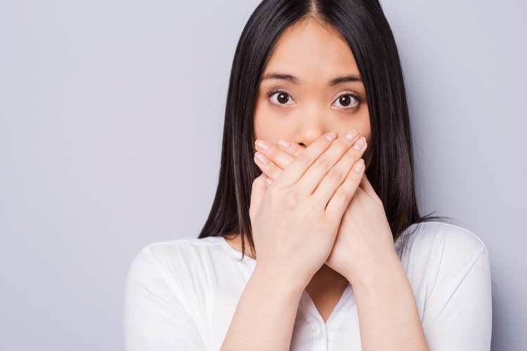 Dark-haired woman with early signs of gum disease covers her mouth with her hands