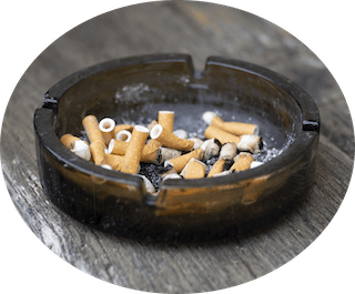 Ashtray with used cigarettes contains tobacco that cause oral cancer