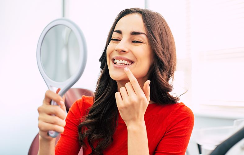 Woman checking her smile in mirror
