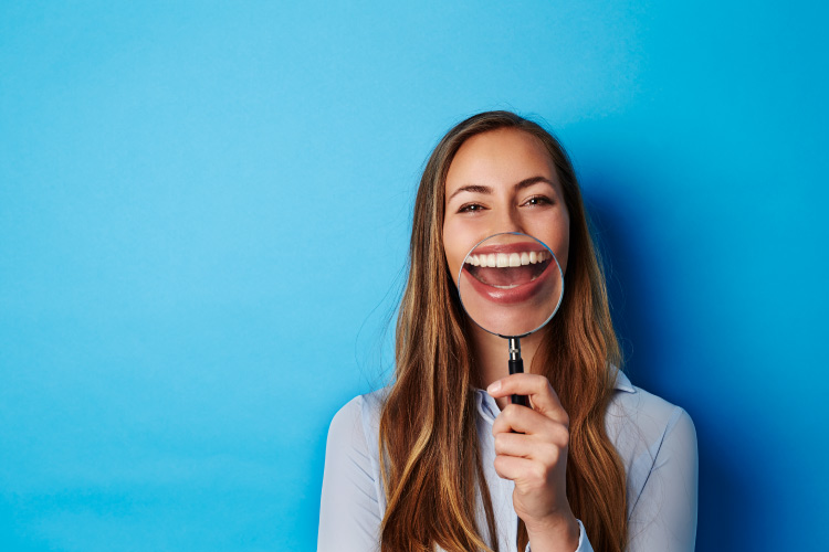 Brunette woman holds a magnifying glass up to her teeth when talking about dental myths and smiles against a blue wall