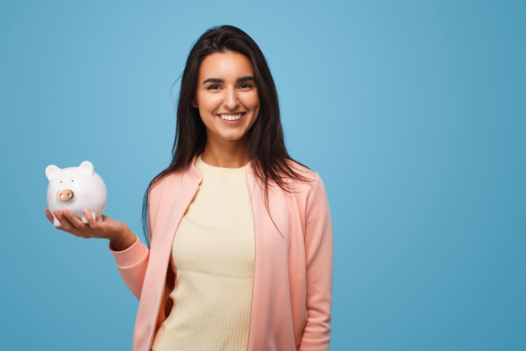Brunette woman wearing a pink cardigan smiles and holds up a white piggy bank against a blue wall