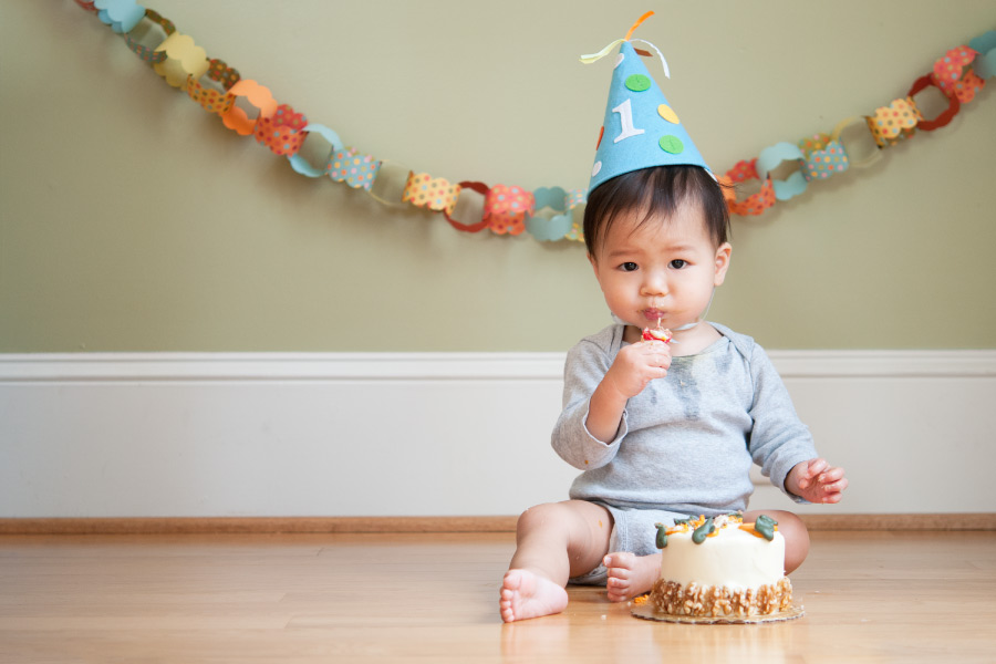 A baby eats cake for his first birthday before his first visit to the dentist