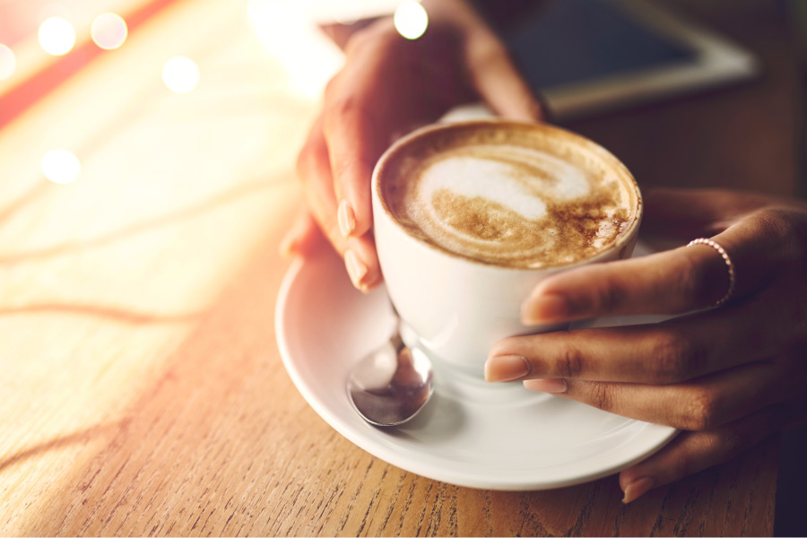 A woman's hand grip a cup of coffee on a white plate with a spoon on a wooden table