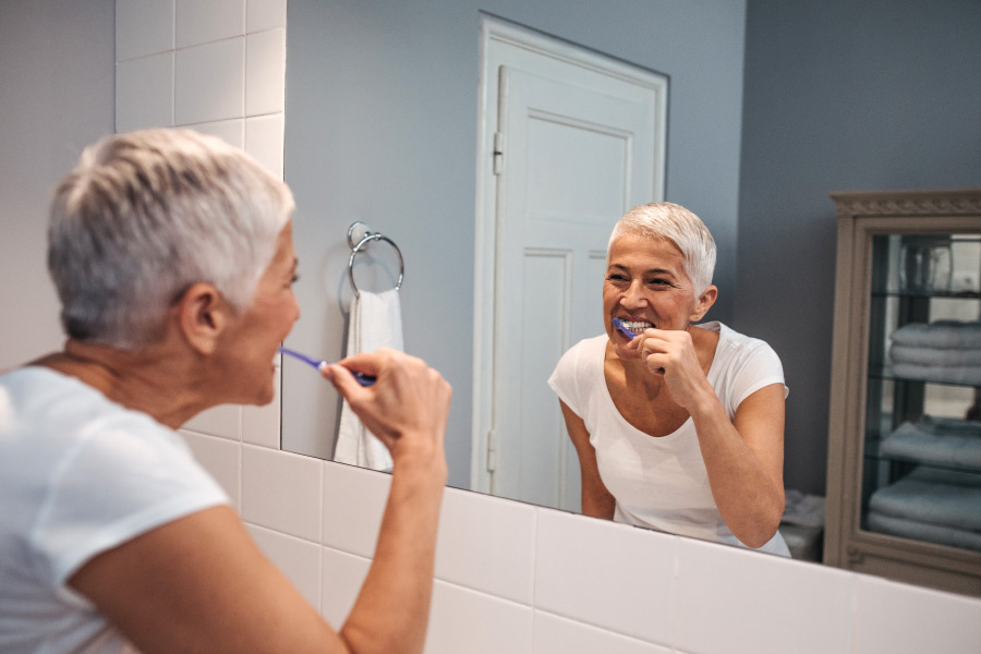 Senior woman brushes her teeth over the bathroom sink to keep her teeth and gums healthy