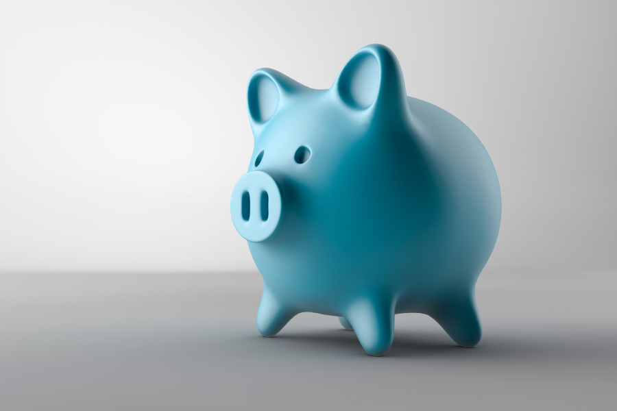 Blue piggy bank on a gray background for a post about saving money with a dental membership plan