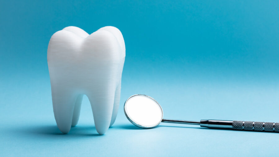 A white tooth next to a special dental mirror against a blue background at the dentist in Westerville, OH